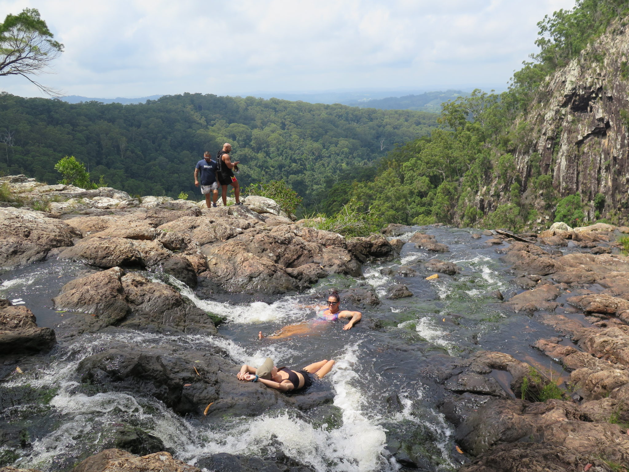 Tourists enjoy at dip at the top of Minyon Falls